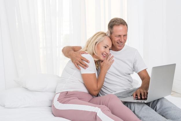Coppie felici del colpo medio con il computer portatile nella camera da letto Foto Gratuite