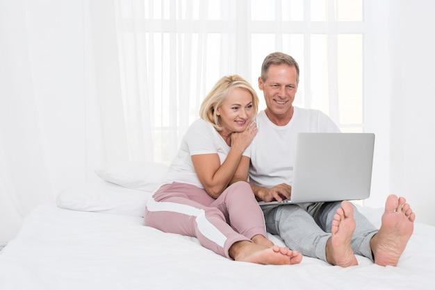 Coppie felici della foto a figura intera con il computer portatile nella camera da letto Foto Gratuite