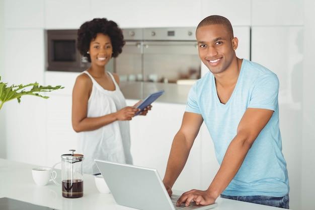 Coppie felici dentro nella cucina facendo uso del computer portatile e del ridurre in pani Foto Premium