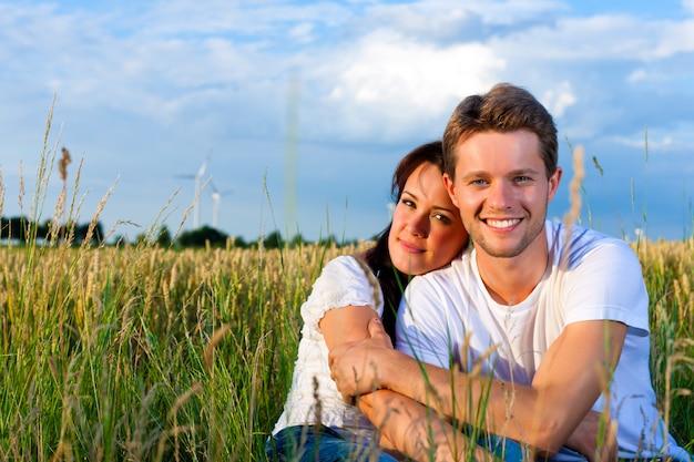 Coppie felici di estate nell'erba di un prato Foto Premium