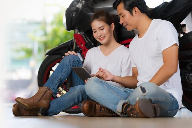 Coppie felici facendo uso della compressa digitale a casa con un fondo del motociclo Foto Premium