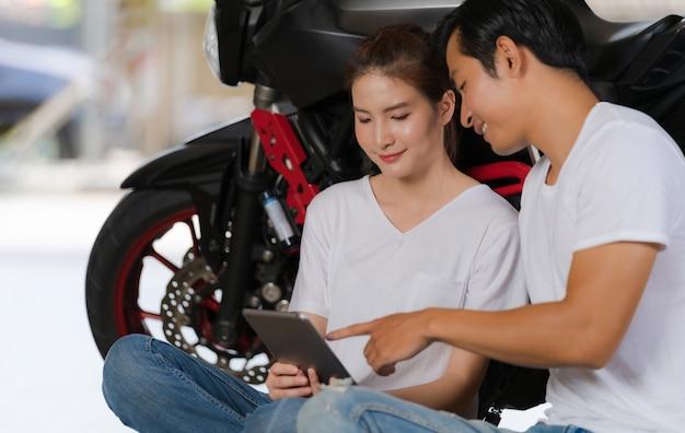 Coppie felici facendo uso della compressa digitale a casa con una motocicletta Foto Premium