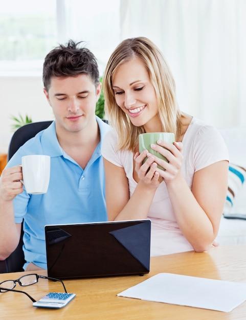 Favoloso Coppie felici facendo uso di un computer portatile che si siede  GF38