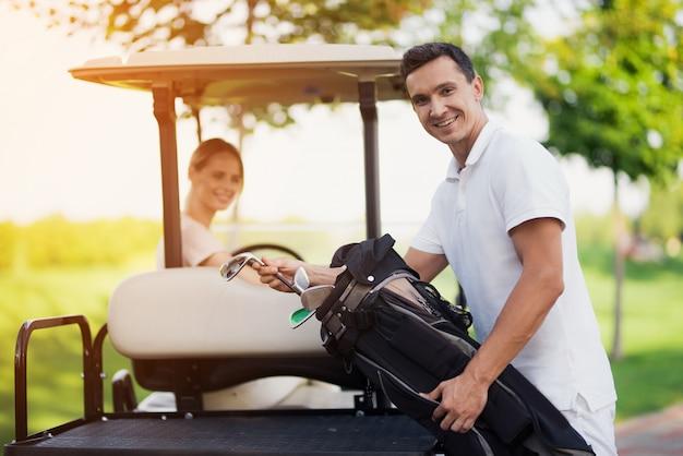 Coppie felici in attrezzatura di golf di trasporto del carrello di golf. Foto Premium