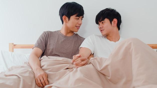 Coppie gay asiatiche belle che parlano sul letto a casa. il giovane ragazzo asiatico lgbtq + rilassa felicemente il riposo insieme trascorre del tempo romantico dopo il risveglio in camera da letto nella casa moderna al mattino. Foto Gratuite