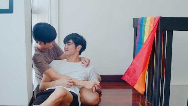 Coppie gay asiatiche che si trovano e che abbracciano sul pavimento a casa. i giovani uomini asiatici lgbtq + che baciano felici si rilassano insieme riposano trascorrere del tempo romantico in salotto con la bandiera arcobaleno a casa moderna al mattino. Foto Gratuite