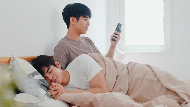 Coppie gay asiatiche facendo uso del telefono cellulare a casa. young asia lgbtq + uomo felice rilassarsi riposo dopo il risveglio, controllare i social media mentre il suo ragazzo dorme sdraiato sul letto nella camera da letto a casa la mattina. Foto Gratuite