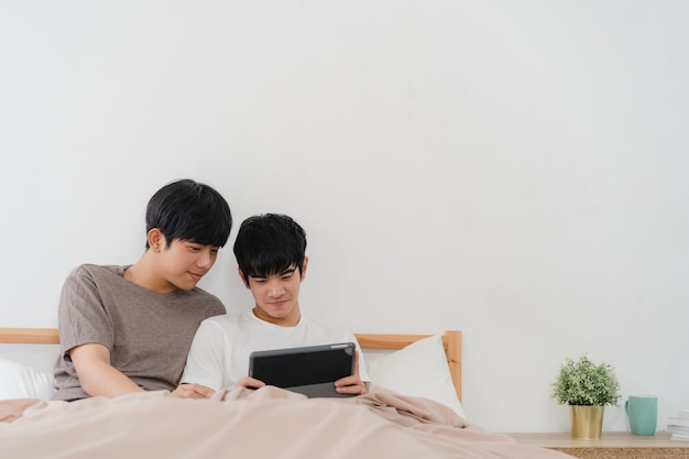 Coppie gay asiatiche facendo uso della compressa a casa. i giovani uomini asiatici lgbtq + si rilassano felici insieme dopo il risveglio, controllano la posta e i social media sdraiati sul letto in camera da letto a casa la mattina. Foto Gratuite