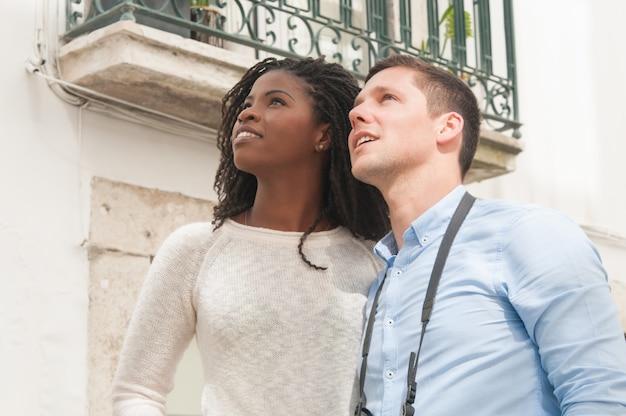 Coppie interrazziali attraenti sorridenti facendo un giro turistico all'aperto Foto Gratuite