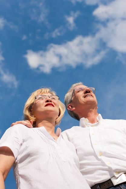 Coppie mature che esaminano il cielo blu Foto Premium