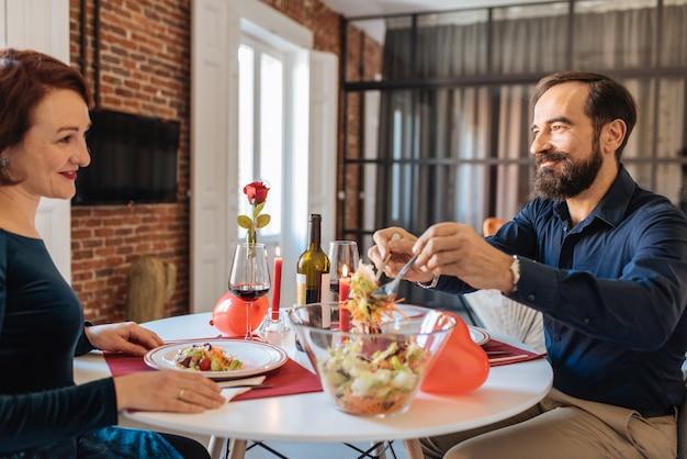 Coppie mature che hanno una cena romantica a casa per il giorno di biglietti di s. valentino Foto Premium