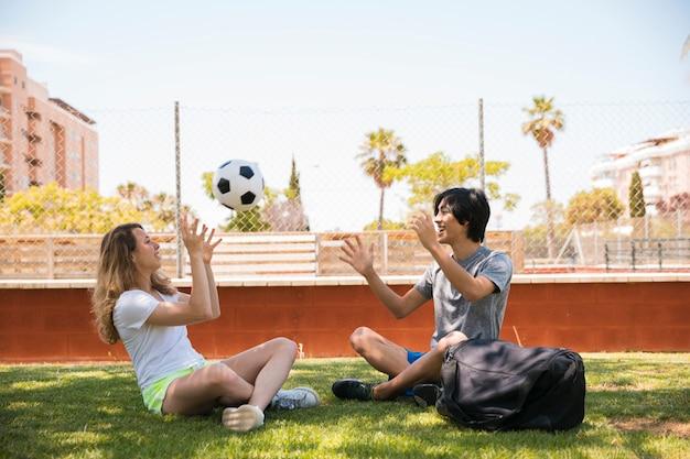Coppie multirazziali che gettano pallone da calcio mentre sedendosi sull'erba Foto Gratuite