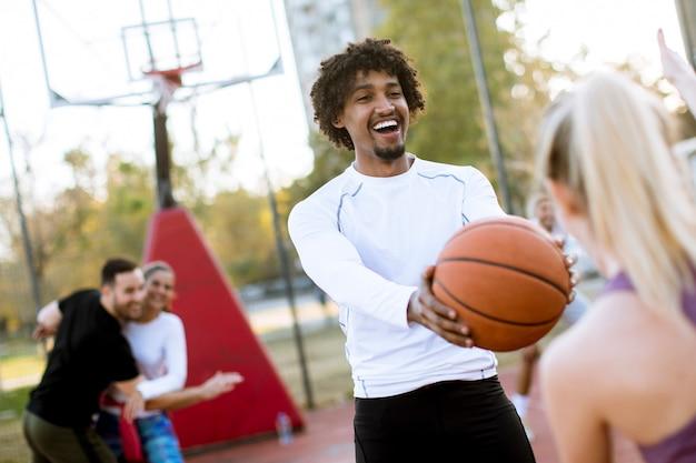 Coppie multirazziali che giocano pallacanestro sulla corte all'aperto Foto Premium
