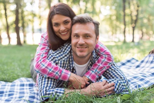 Coppie romantiche felici che si trovano sulla coperta blu al parco che guarda l'obbiettivo Foto Gratuite