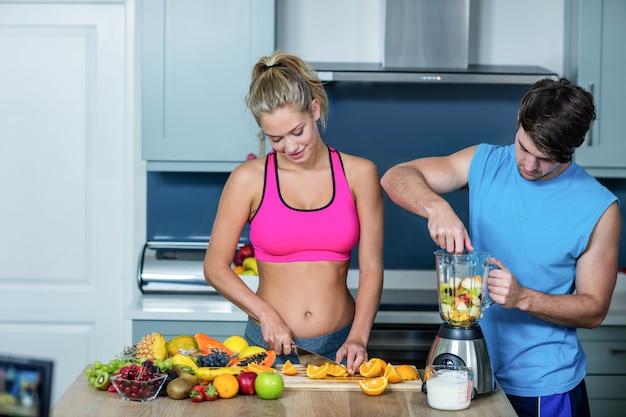 Coppie sane che preparano un frullato in cucina Foto Premium