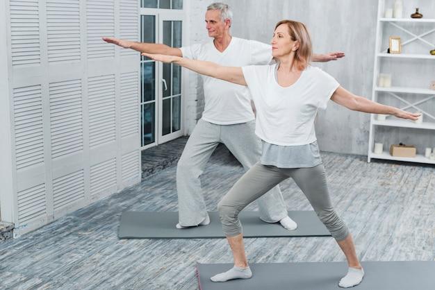 Coppie sane che si esercitano sulla stuoia di yoga a casa Foto Gratuite