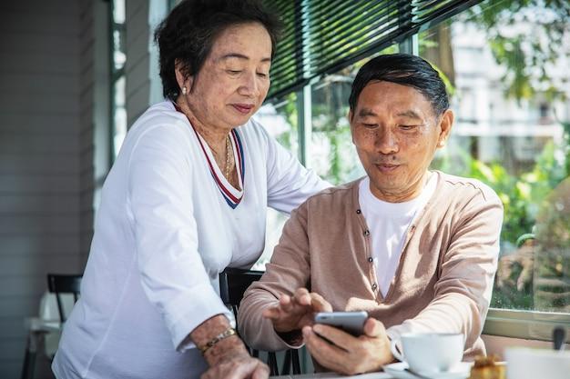 Coppie senior asiatiche che esaminano smartphone mentre ora del the Foto Premium