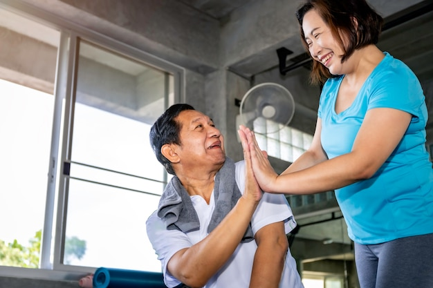 Coppie senior asiatiche che sorridono in abiti sportivi che si esercitano alla palestra. Foto Premium