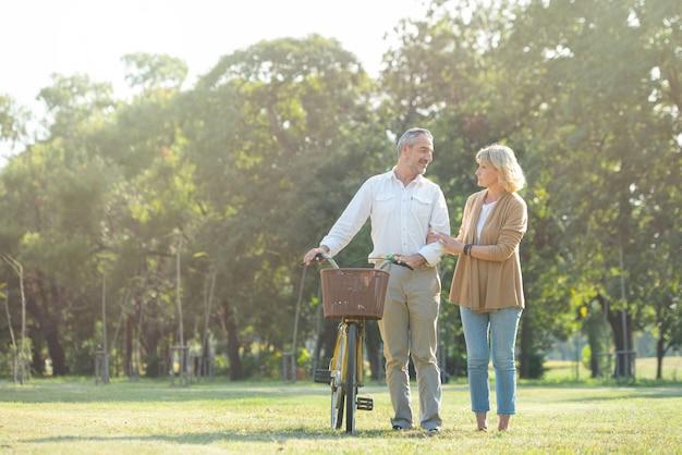 Coppie senior attive allegre con la bicicletta che camminano insieme attraverso il parco. attività perfette per le persone anziane in età pensionabile. Foto Premium