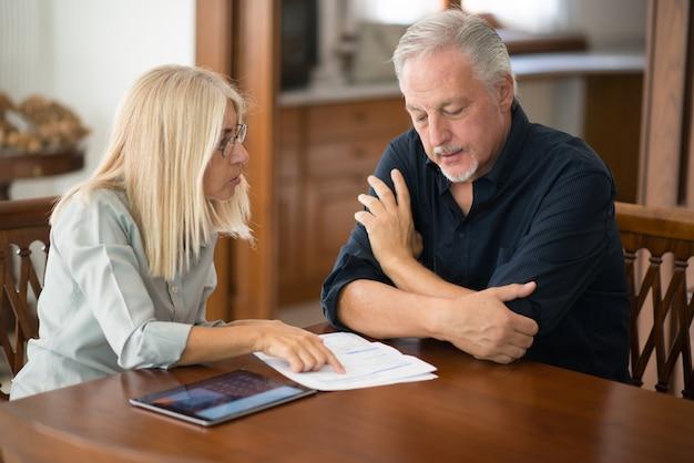Coppie senior che calcolano insieme le loro spese di soggiorno Foto Premium