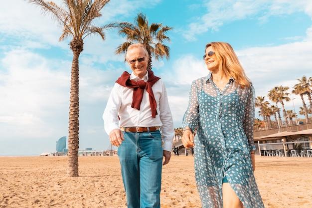 Coppie senior che camminano sulla spiaggia a barcellona Foto Premium