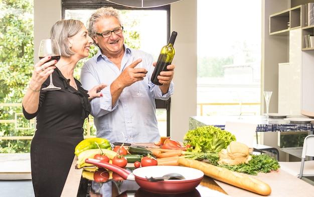Coppie senior che cucinano alimento sano e che bevono vino rosso alla cucina della casa Foto Premium