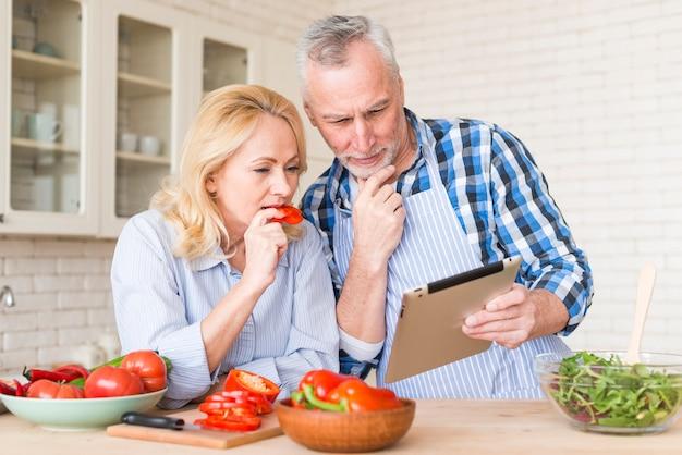 Coppie senior che esaminano compressa digitale mentre preparando l'alimento nella cucina Foto Gratuite