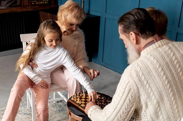Coppie senior che giocano scacchi insieme ai loro nipoti Foto Gratuite