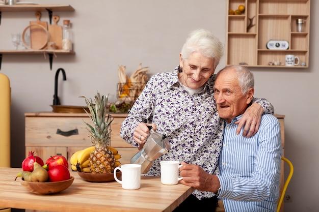 Coppie senior che mangiano caffè nella cucina Foto Gratuite