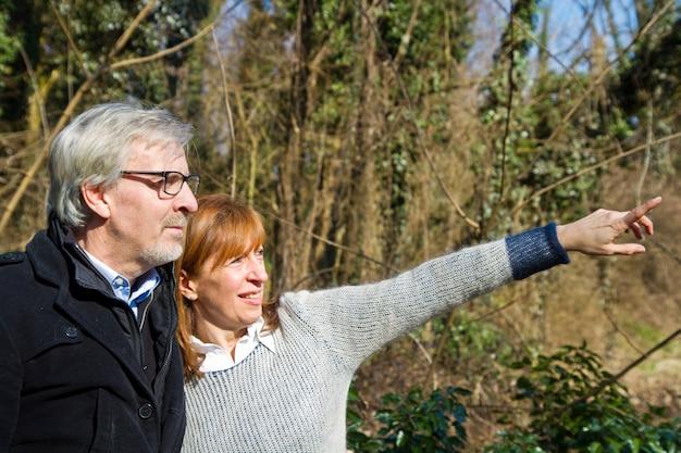 Coppie senior che mostrano qualcosa nel parco Foto Premium