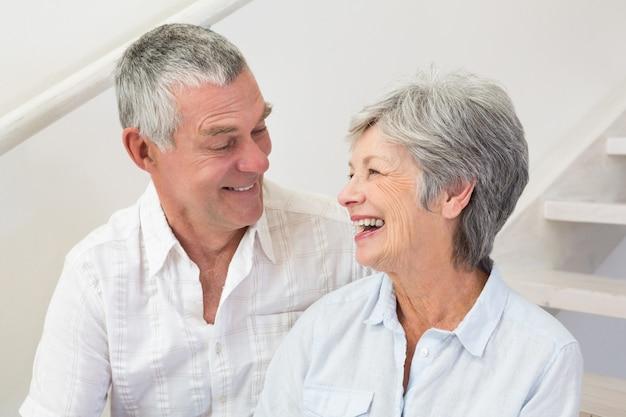 Coppie senior che si siedono sulle scale che sorridono a vicenda Foto Premium