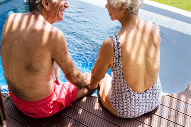 Coppie senior che si tengono per mano dalla piscina Foto Premium