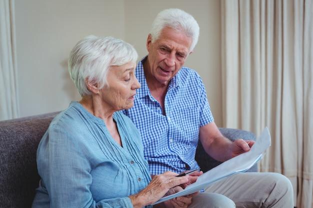 Coppie senior con le fatture mentre sedendosi sul sofà Foto Premium