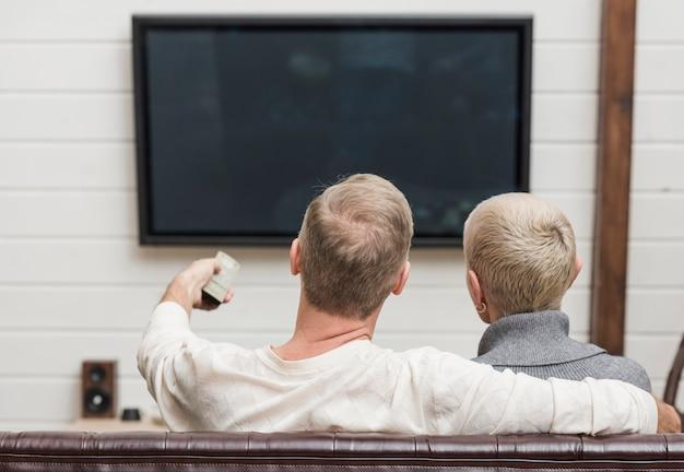 Coppie senior di vista posteriore che guardano qualcosa sulla tv Foto Gratuite