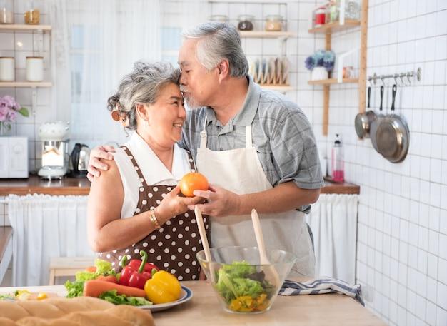 Coppie senior divertendosi nella cucina con alimento sano - pensionati che cucinano pasto a casa con l'uomo e la donna che preparano pranzo con le bio- verdure - concetto anziano felice con il pensionato divertente maturo. Foto Premium