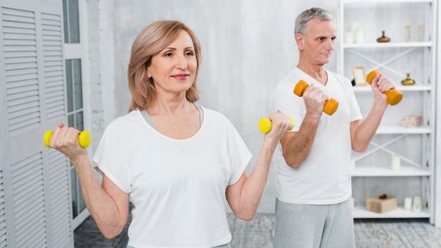 Coppie senior felici che si esercitano usando i dumbbells Foto Gratuite