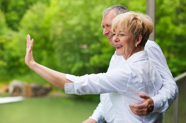 Coppie senior felici sulle mani d'ondeggiamento del ponte Foto Premium