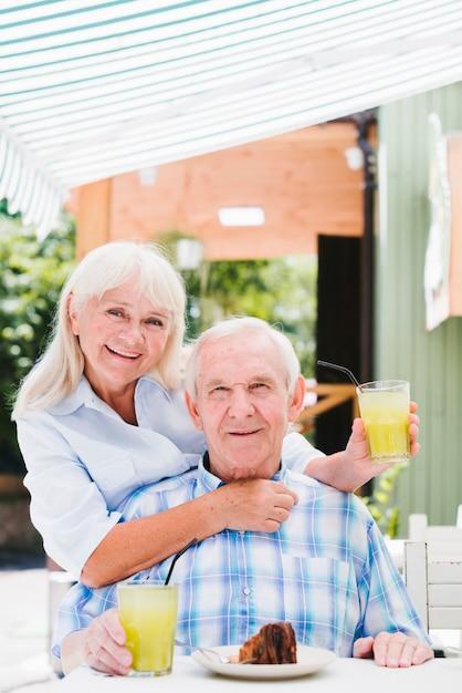 Coppie senior soddisfatte che abbracciano nel caffè sul terrazzo che gode della bevanda e del dolce rinfrescanti Foto Gratuite