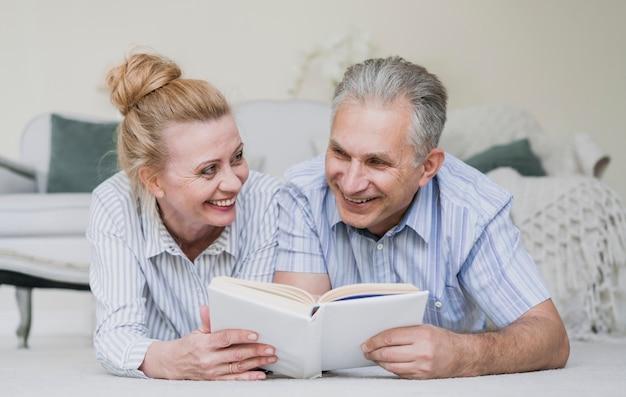 Coppie senior sveglie insieme ad un libro Foto Gratuite