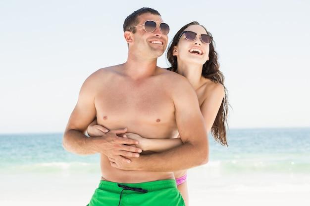 Coppie sorridenti che abbracciano sulla spiaggia Foto Premium