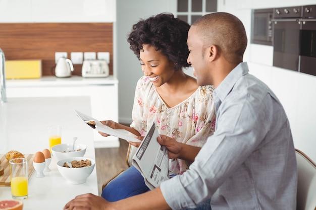 Coppie sorridenti che leggono rivista e documenti durante la prima colazione in cucina Foto Premium