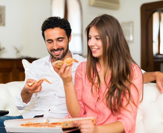 Coppie sorridenti che mangiano pizza mentre sedendosi sullo strato Foto Premium