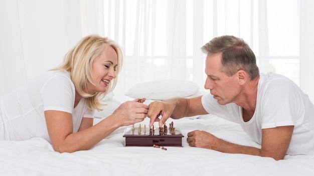 Coppie sorridenti del colpo medio che giocano scacchi Foto Gratuite