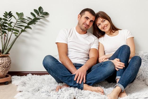 Coppie sorridenti di vista frontale che si siedono sul pavimento Foto Gratuite