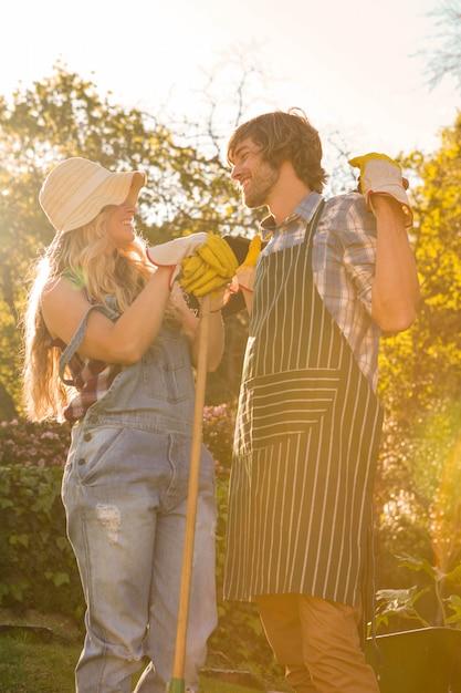 Coppie sorridenti nel giardino che tiene un rastrello Foto Premium