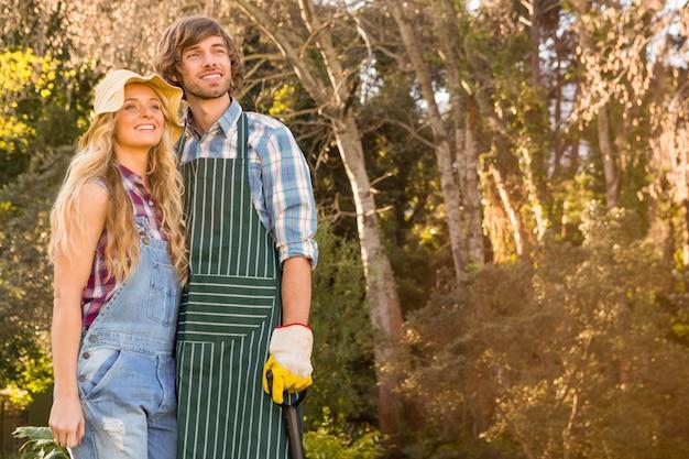 Coppie sorridenti nel giardino che tiene una pala Foto Premium