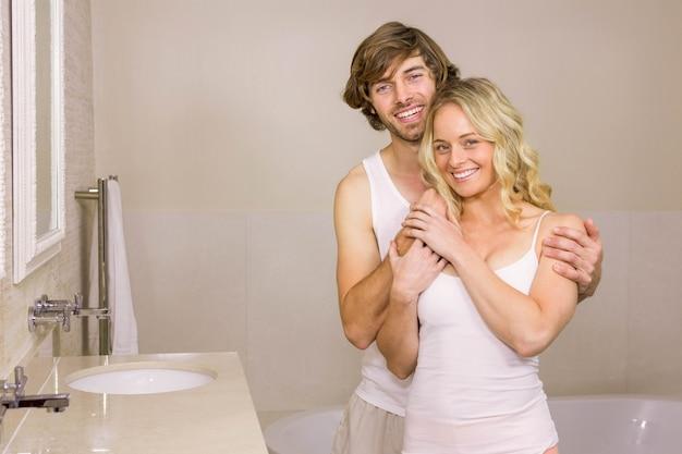 Coppie sveglie che abbracciano nel bagno a casa Foto Premium