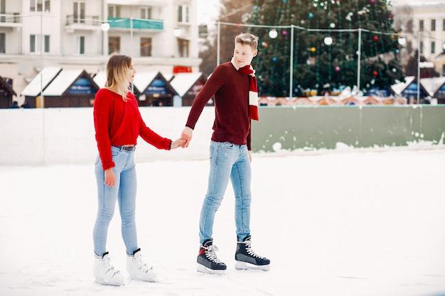 Coppie sveglie in maglioni rossi divertendosi in un'arena di ghiaccio Foto Gratuite
