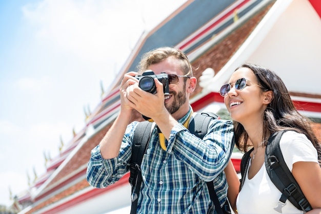 Coppie turistiche interraziali che prendono le foto durante il viaggio di vacanza estiva a bangkok tailandia Foto Premium