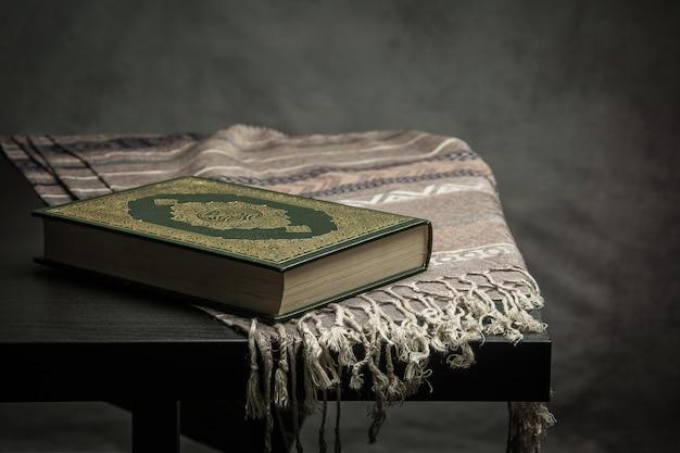 Corano - libro sacro dei musulmani (oggetto pubblico di tutti i musulmani) sul tavolo, natura morta Foto Premium